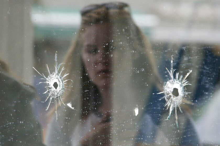 FILE - In this May 24, 2014 file photo, a woman looks at the bullet holes on the window of IV Deli Mark where a mass shooting took place near the University of California, Santa Barbara campus, in the Isla Vista beach community of Santa Barbara, Calif.  In response to the killing rampage of Elliot