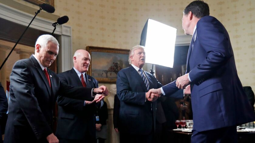 President Trump greets FBI Director James Comey at the White House in January. At left are Vice President Mike Pence and Secret Service Director Joseph Clancy.