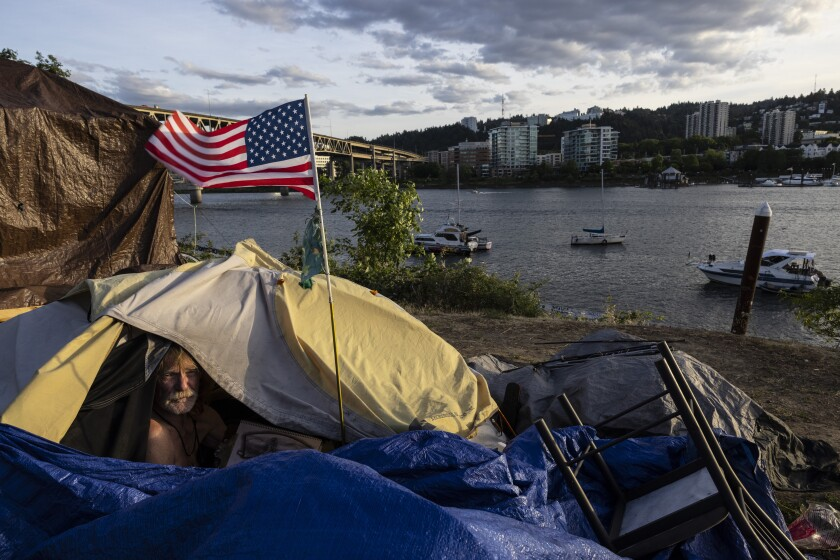 A man peeks out of a flap of a tent that has a U.S. flag attached.