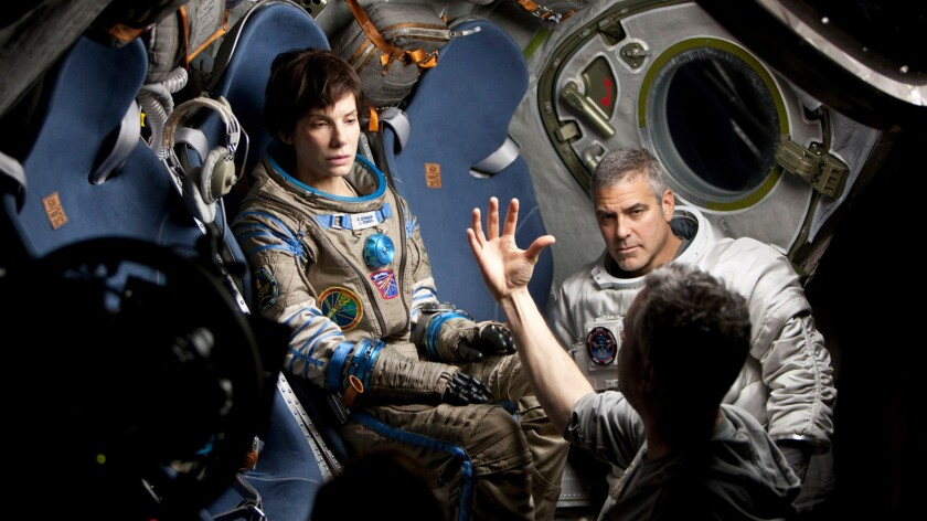 "Sandra Bullock and George Clooney talk with director Alfonso Cuaron on the set of ""Gravity."""