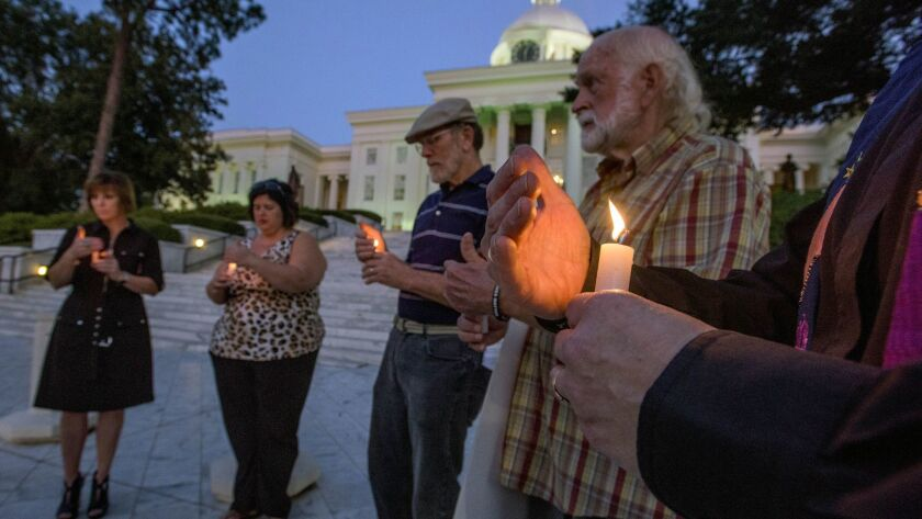 Concerned citizens gather for a candlelight vigil for convicted murderer Tommy Arthur on the steps o