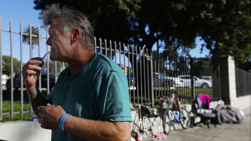 A homeless veteran shaves his face outside the West Los VA Medical Center gate, on December 13, 2017.