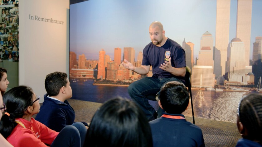 """A New York City fireman speaks to children in a scene from the documentary """"What Happened on September 11."""""""