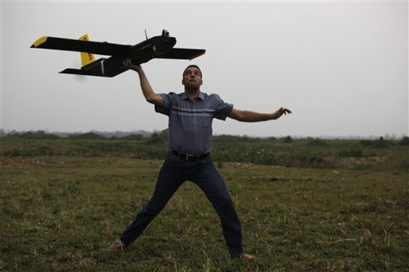 Remo Peduzzi, managing director of ResearchDrones LLC Switzerland prepares to fly an unmanned aircraft or drone at the Kaziranga National Park at Kaziranga in Assam state, India, Monday, April 8, 2013. Wildlife authorities used drones on Monday for aerial surveillance of the sprawling natural game park in northeastern India to protect the one-horned rhinoceros from armed poachers. The drones will be flown at regular intervals to prevent rampant poaching in the park located in the remote Indian s