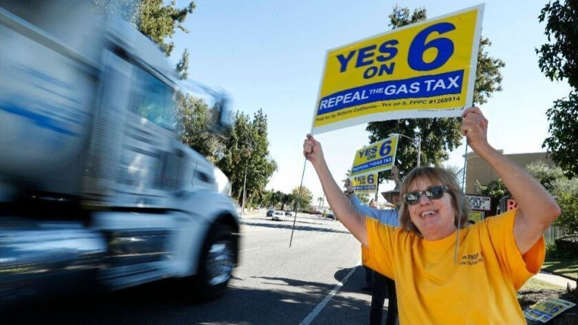 Supporters of Proposition 6 draw the attention of motorists in Pasadena on Oct. 17.