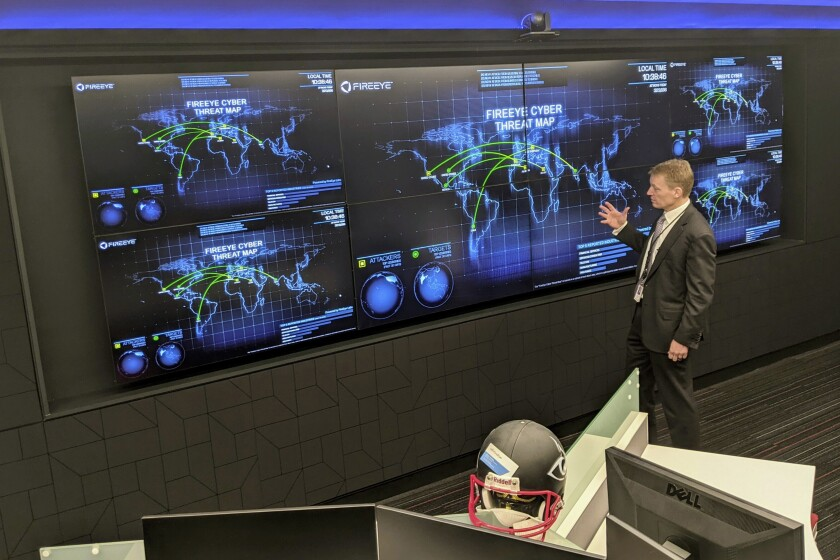 The CEO of FireEye Kevin Mandia gives a tour of the cybersecurity company's unused office space in Reston, Va., Tuesday, March 9, 2021. Mandia said 550 of his employees are working remotely and responding to a recent barrage of cyber breaches, including four different zero-day attacks against Microsoft Exchange. (AP Photo/Nathan Ellgren)