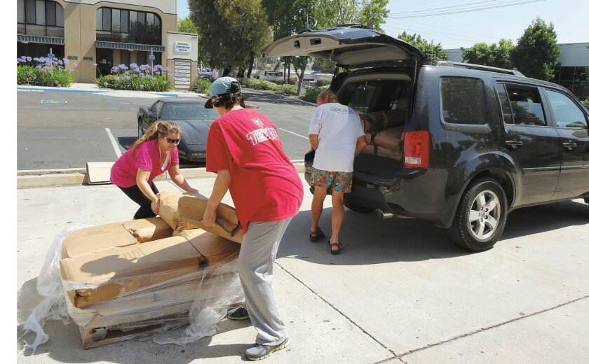 Michela Arredondo (left) and Elsa Blanco, co-founders of San Diego County-based Dog Rescue Without Borders, get help loading dog food from Kelly Burch (right), of Kellen Rescue.
