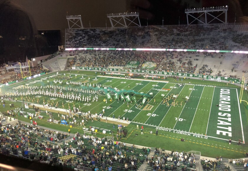 Colorado State cheerleaders lead the football team onto the field at Canvas Stadium before Saturday night's game against San Diego State.