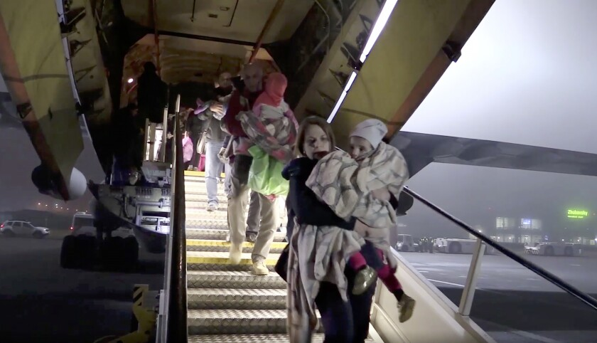 In a photo taken from video, Russian officials carry children from a plane Nov. 18 at Zhukovsky International Airport outside Moscow.