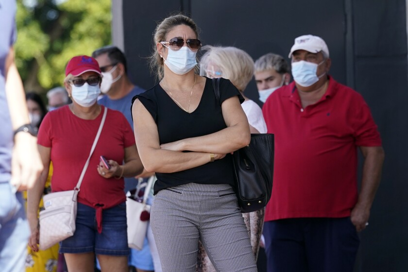 People stand in line for early voting at the John F. Kennedy Library, Tuesday, Oct. 27, 2020, in Hialeah, Fla. Masks are required at some polling places around the country and strongly encouraged in most others as a basic precaution to help keep poll works and others safe from the fast-spreading coronavirus. But mandates tying a face covering to casting a ballot are sure to lead to confrontations on Election Day, and those will almost certainly grab wide attention if they arise in any of the presidential battleground states. (AP Photo/Lynne Sladky)