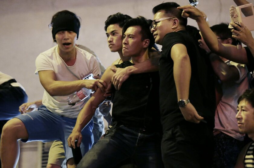 Angry protesters confront each other in Kowloon's crowded Mong Kok district, Saturday, Oct. 4, 2014 in Hong Kong. Clashes broke out Friday as Hong Kong residents and pro-Beijing supporters tried to force pro-democracy activists from the streets they were occupying, reviving the possibility that the weeklong standoff could turn violent despite and attempt by the city's leader to defuse the situation. (AP Photo/Wong Maye-E)