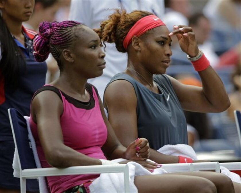 Venus Williams, left, and Serena Williams sit together during a break between games during a doubles match against Raquel Kops-Jones and Abigail Spears during the second round of the 2013 U.S. Open tennis tournament, Saturday, Aug. 31, 2013, in New York. (AP Photo/Mike Groll)