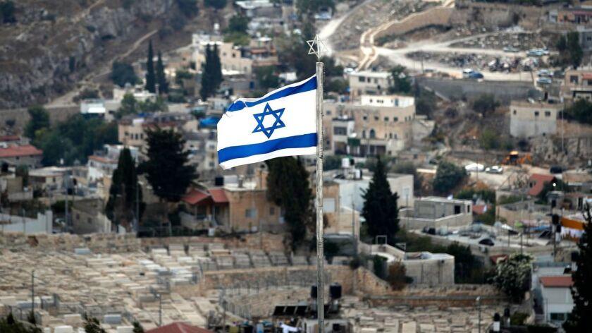 The Israeli flag flutters over the Mount of Olives adjacent to Jerusalem's Old City.