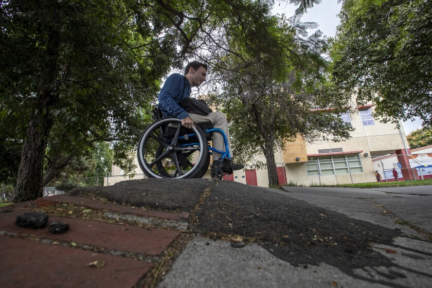 David Radcliff crossing a warped sidewalk in his wheelchair