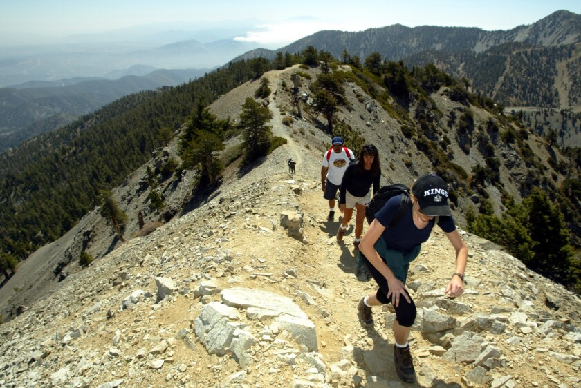 Hikers make it to the top of Mt. Baldy in the San Gabriel Mountains. A federal judge has ruled that visitors to Southern California's four national forests do not need to buy an Adventure Pass if they are only hiking and do not use forest facilities.