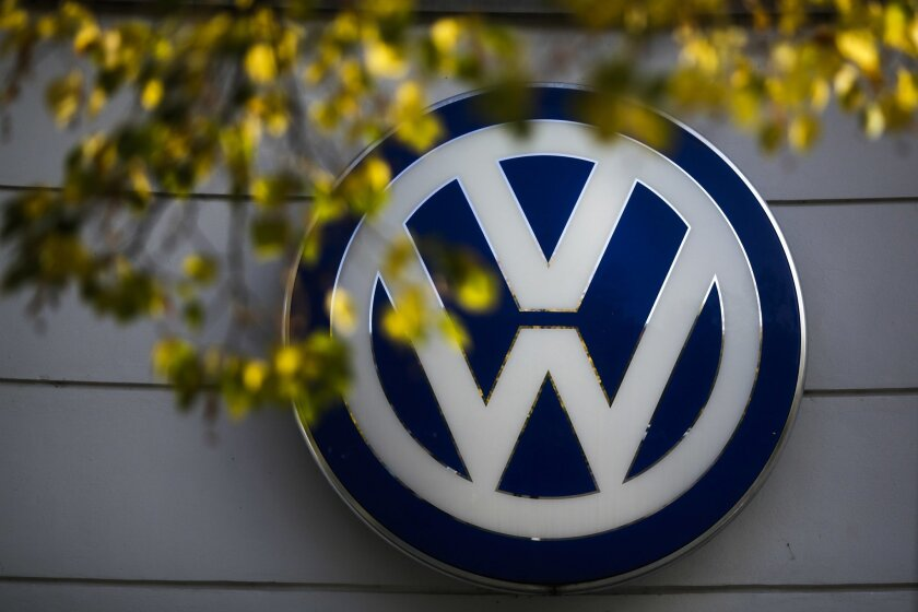 FILE - In this Oct. 5, 2015, file photo, the VW sign of Germany's Volkswagen car company is displayed at the building of a company's retailer in Berlin. Volkswagen Truck & Bus, an arm of the German automaker Volkswagen, is buying a minority stake in Navistar. The two companies also said Tuesday, Se