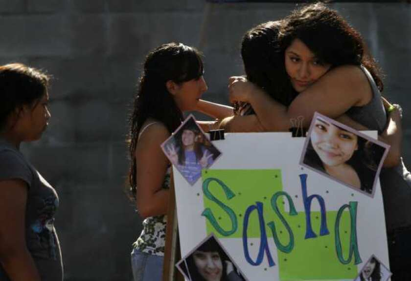Yuritzi Meza, 16, (far right) hugs Jessica Valiente, (second from right) at a fundraiser for the family of 15-year-old Sasha Rodriguez, who died from a suspected drug overdose during the Electric Daisy Carnival, at Allessandro Elementary School in Los Angeles. Rodriguez's teammates on the 1st Impressions drill team, a hip hop dance team, helped organize the fundraiser for the family.