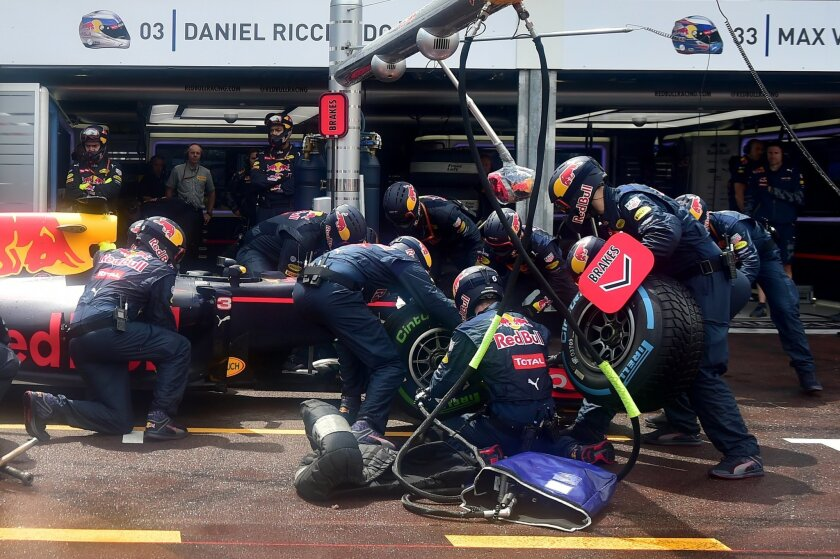 Technicians change tyres to Red Bull driver Daniel Ricciardo of Australia in the pit lane during the Formula One Grand Prix at the Monaco racetrack in Monaco on Sunday May 29, 2016. (AP Photo/Andrej Isakovic/Pool)