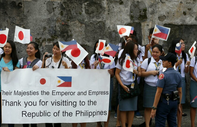 Students line up the route with Japanese and Philippine flags to welcome visiting Japan's Emperor Akihito and Empress Michiko for another function at Fort Santiago Thursday, Jan. 28, 2016 in Manila, Philippines. The 82-year-old Akihito is paying his respects at memorials for both the Philippine and the Japanese war dead during a five-day state visit.(AP Photo/Bullit Marquez)