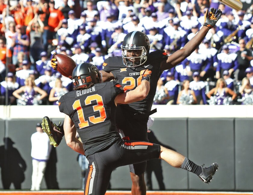 Oklahoma State wide receiver James Washington (28) celebrates with teammate wide receiver David Glidden (13) in the first of an NCAA college football game against TCU in Stillwater, Okla., Saturday, Nov. 7, 2015. (AP Photo/Sue Ogrocki)