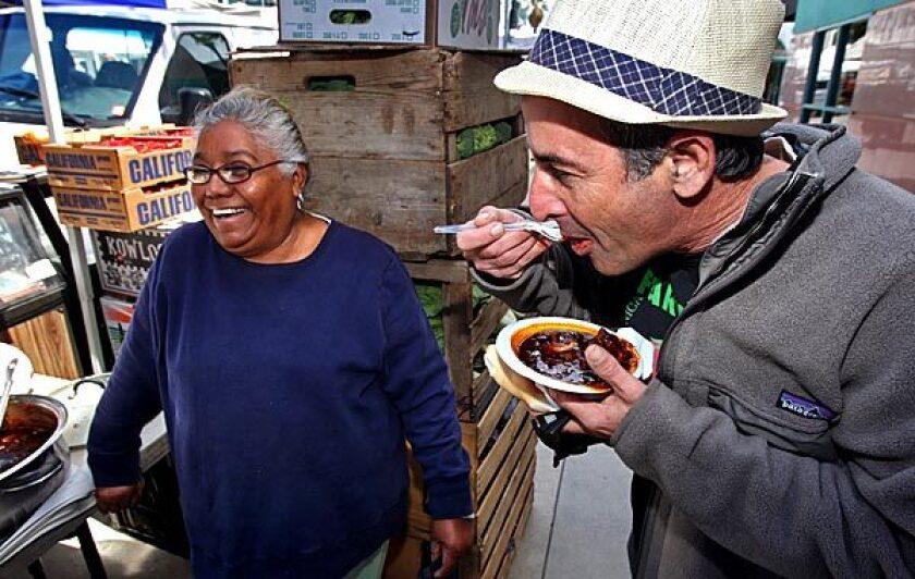 Sotera Jaime of Jaime Farms serves puerco con chile negro to Alex Weiser at the Santa Monica farmers market.
