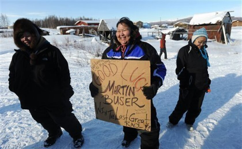 Ann Neglaska of Kaltag holds a sign that four-time Iditarod champion Martin Buser signed the last time he won the Iditarod in 2002. Buser autographed the sign again this year and she hopes he becomes a champion again. (AP Photo/Anchorage Daily News, Bill Roth)