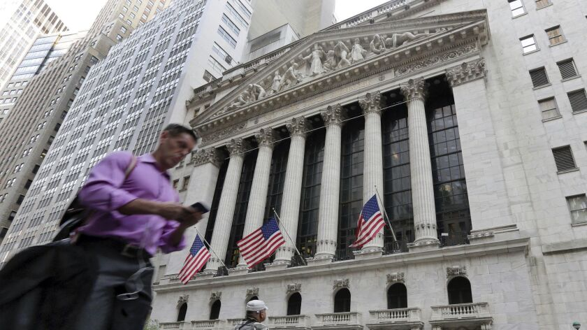 FILE - In this June 24, 2016, file photo, a man walks by the New York Stock Exchange. The U.S. stock