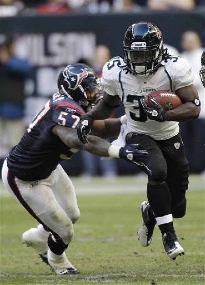 Jacksonville Jaguars running back Deji Karim (35) gets past Houston Texans linebacker Kevin Bentley (57) for a first down in the second quarter of an NFL football game Sunday, Jan. 2, 2011, in Houston. (AP Photo/David J. Phillip)