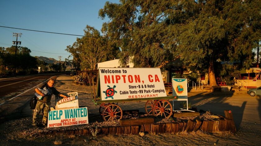 A man tends to signs beside a road leading into Nipton, Calif., in August 2017.