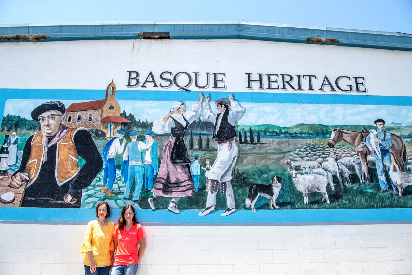 Jenny Poncette, left, and her daughter, Christiane Camou, pose beneath a mural by artist Tom Zachery in the parking lot of their restaurant Wool Growers in Bakersfield.