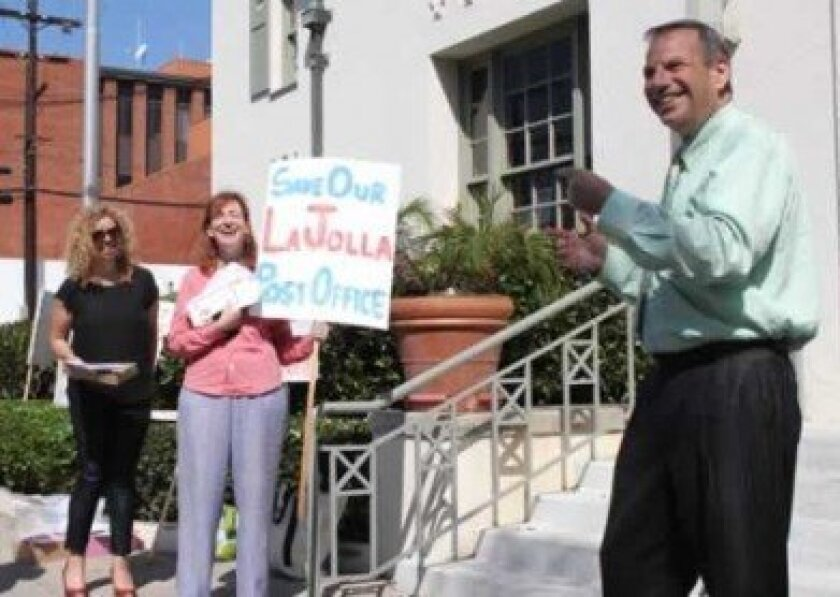 Congressman Bob Filner, who authored his own legislation aimed at saving the Wall Street post office, keeps the crowd amused as Athina Singer (far left) and Leslie Davis of the Save Our La Jolla Post Office Task Force look on.       PAT SHERMAN