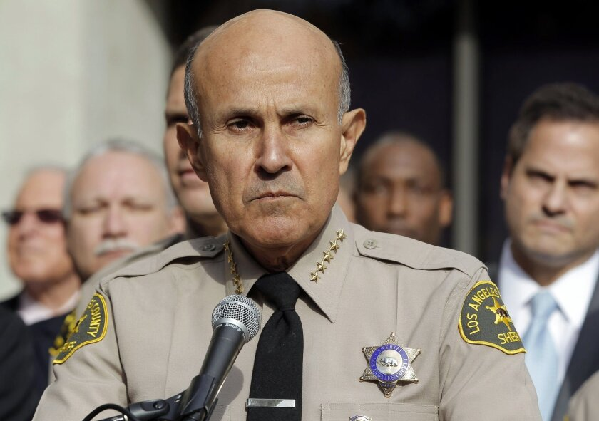 """FILE - In this Jan. 7, 2014, file photo, Los Angeles County Sheriff Lee Baca announces his retirement at a news conference at Sheriff's Headquarters Bureau in Monterey Park, Calif. Baca signed a plea agreement that said he ordered deputies to intimidate an FBI agent and """"do everything but put handc"""