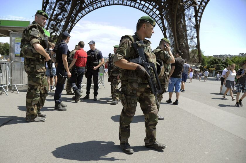 "Soldiers patrol under the Eiffel Tower in Paris as part of the Vigipirate security alert system on June 26. Earlier that day, a factory in the Rhone-Alpes region was hit in an attack defined as ""Islamist terrorism"" by the French prime minister."
