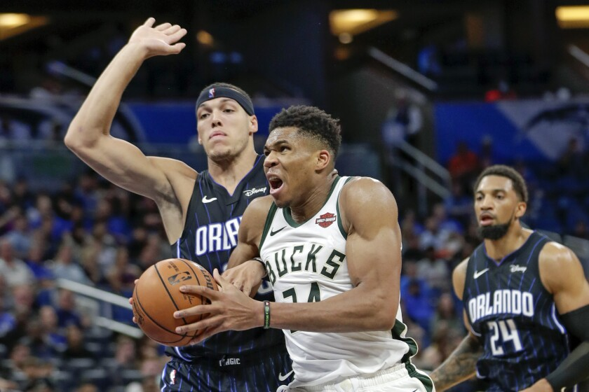 Milwaukee Bucks' Giannis Antetokounmpo goes in for a shot as he gets past Orlando Magic's Aaron Gordon, left, and Khem Birch during the second half of an NBA basketball game Friday, Nov. 1, 2019, in Orlando, Fla. (AP Photo/John Raoux)