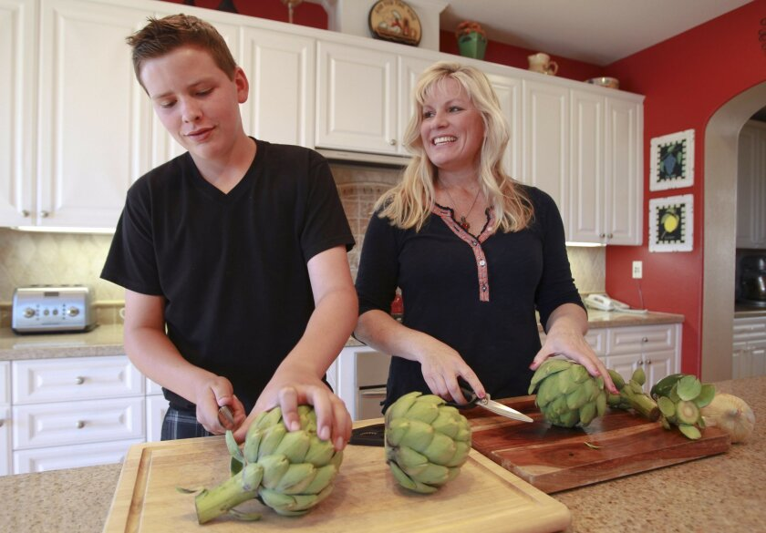 Lori Lange prepares artichokes for steaming with her 12-year-old son Brooks at their home near Carmel Valley in San Diego on Friday.