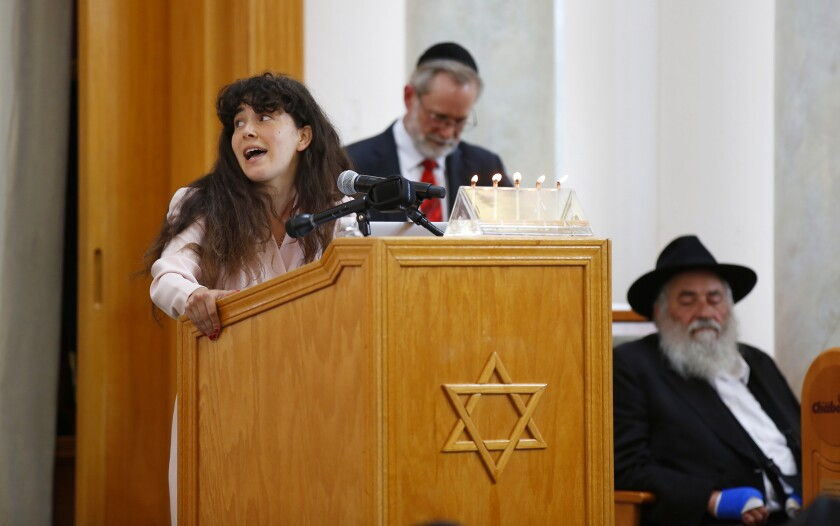 Looking over at a picture of her mom, Hannah Kaye, 22, speaks about her mother Lori Gilbert-Kaye, 60, during a memorial service at the Chabad of Poway on April 28, 2019 in Poway, California. Gilbert-Kaye was killed by a gunman at the synagogue on April 27. Rabbi Yisroel Goldstein, at right, was also injured in the attack.