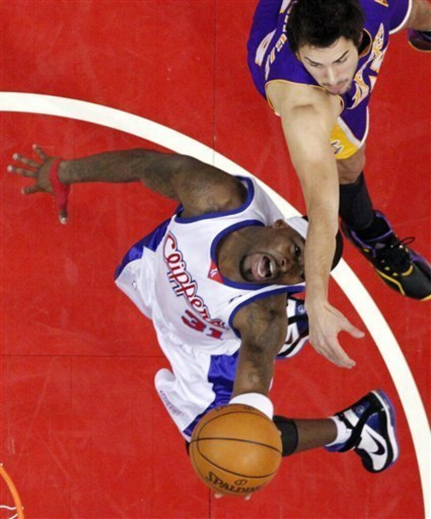 Los Angeles Clippers forward Ricky Davis, below, goes up for a shot as Los Angeles Lakers guard Sasha Vujacic of Slovenia during the first half of their NBA basketball game, Wednesday, Jan. 6, 2010, in Los Angeles. (AP Photo/Mark J. Terrill)