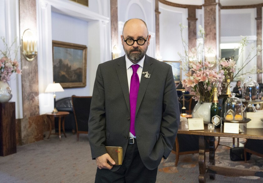 Novelist Carlos Ruiz Zafon holds a book in the lobby of a hotel in Hamburg