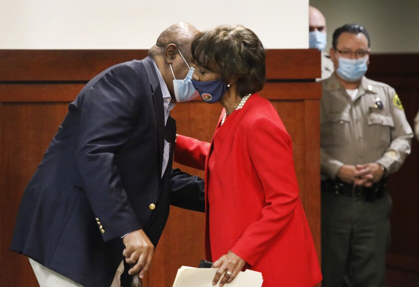 Los Angeles County Dist. Atty. Jackie Lacey kisses her husband, David, in a courtroom