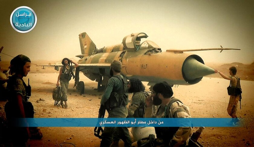 In a Sept. 10 image from the Twitter account of Syria's Nusra Front, fighters from the group gather around a Syrian government aircraft after they seized the Abu Duhur air base.