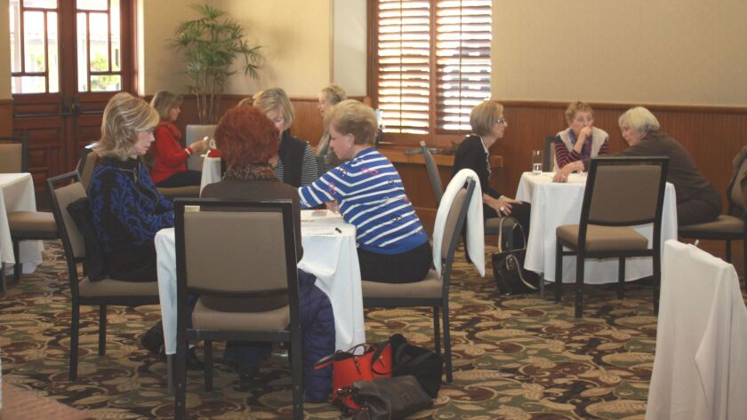In tables of four, women gather to play table games and help raise money for St. Germaine Children's Charity.