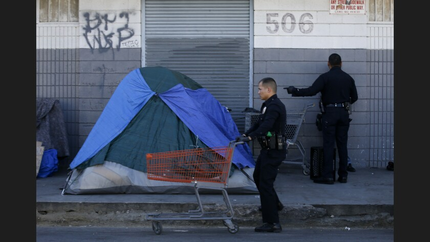 LAPD officers find several shopping carts in the homeless encampments on Stanford Avenue near 5th Street in downtown Los Angeles during a cleanup of skid row.
