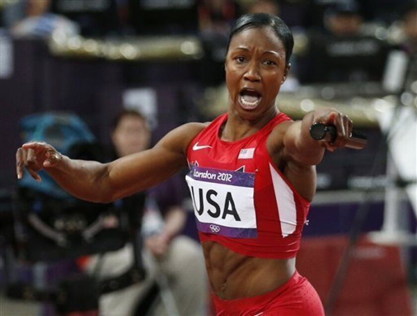 Carmelita Jeter of the United States crosses the finish line in the women's 4x400-meter relay final to win gold during the athletics in the Olympic Stadium at the 2012 Summer Olympics, London, Friday, Aug. 10, 2012. The United States relay team set a new world record with a time of 40.82 seconds. (AP Photo/Matt Dunham)