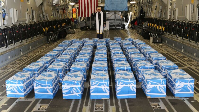 A U.S. Army chaplain, Col. Sam Lee, blesses 55 cases of remains returned by North Korea at Osan Air Base in Pyeongtaek, South Korea, on July 27.