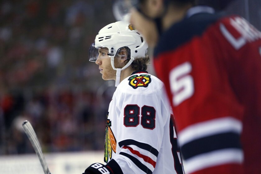 Chicago Blackhawks right wing Patrick Kane, left, and New Jersey Devils defenseman Adam Larsson wait for the puck to drop during the first period of an NHL hockey game, Friday, Nov. 6, 2015, in Newark, N.J. (AP Photo/Julio Cortez)