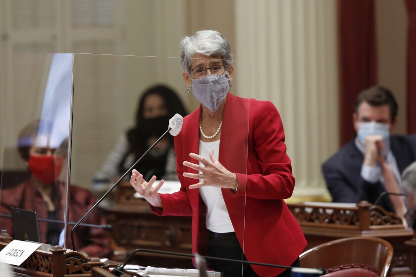 State Sen. Hannah-Beth Jackson wears a mask and speaks behind plexiglass on the floor of the California Senate