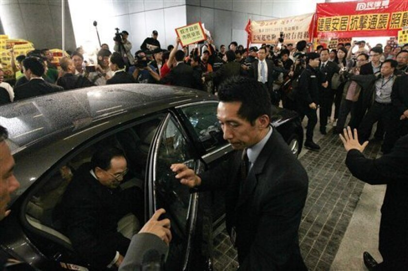 Hong Kong Chief Executive Donald Tsang, left, arrives to deliver his last policy speech at the new Legislative Council building in Hong Kong Wednesday, Oct. 12, 2011. Hong Kong will resume a program to sell thousands of affordable apartments a year, the city's leader said Wednesday as he unveiled a key measure in his annual policy speech aimed at cooling public anger over the city's widening rich-poor gap. (AP Photo/Kin Cheung)