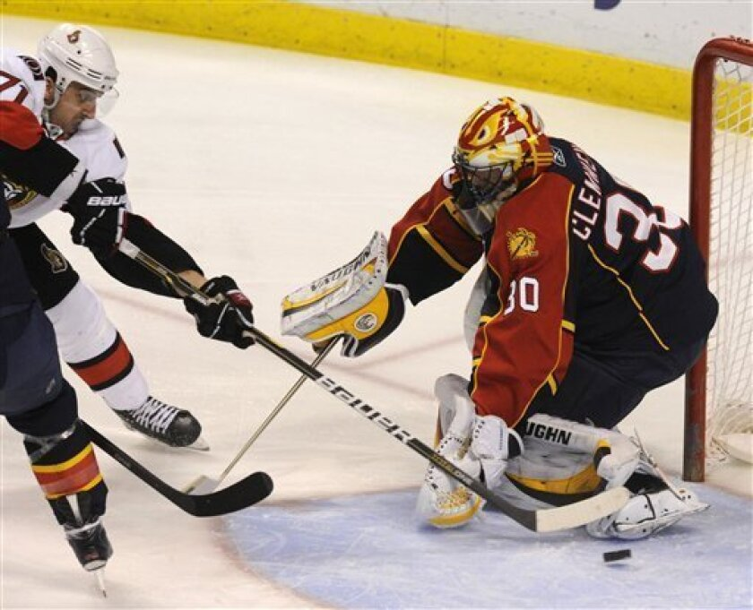 Ottawa Senators' Nick Foligno. left, gets a shot past Florida Panthers goalie Scott Clemmensen, right, to score the first goal during the first period of an NHL hockey game on Thursday, March 31, 2011, in Sunrise, Fla. (AP Photo/Rick Silva)