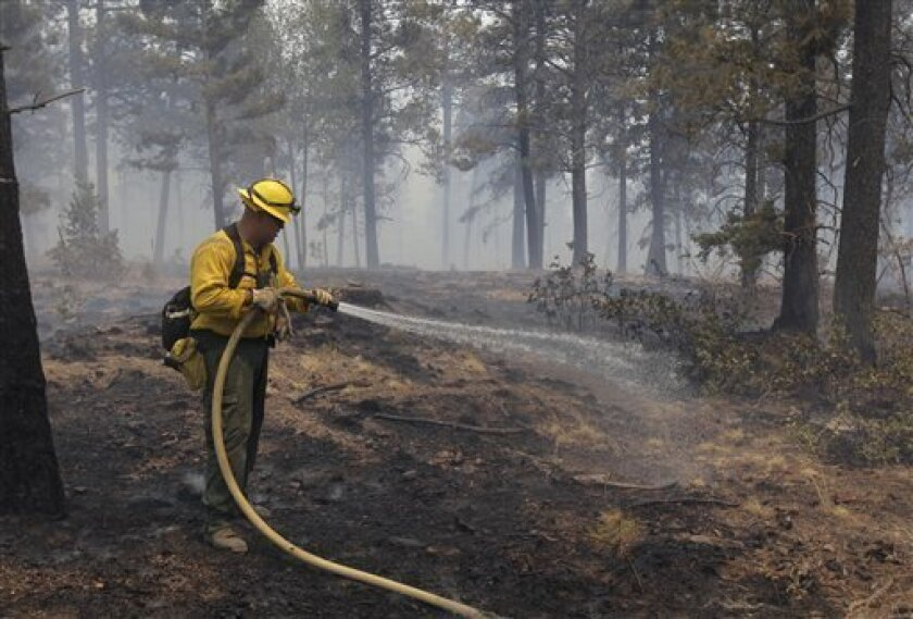 Firefighter Abraham Diaz, of Apple Valley, Calif., sprays water on a hot spot while battling the Las Conchas fire near Los Alamos, N.M., Wednesday, June 29, 2011. As crews fight to keep the wildfire from reaching the country's premier nuclear-weapons laboratory and the surrounding community, scient