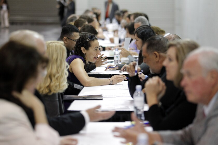 Job seekers have their resumes reviewed at a job fair expo in Anaheim last summer. Employment among California women slipped from December 2010 through December 2012 even while men were steadily finding new work, and their pay has slipped too.